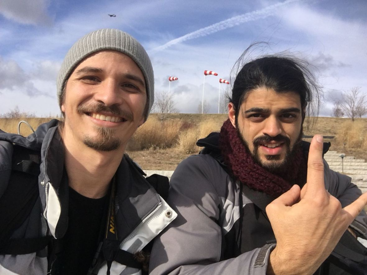 Two man are depicted in the photo. In the background a dry grassland with blue skies. The man have facial hair, are wearing winter clothes and are looking happy.